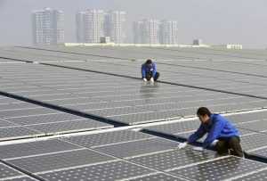 Technicians maintain solar panels on a roof at a solar power plant in Wuhan, Hubei province, January 12, 2010. The Chinese government aims to boost renewable energy generating capacity in the country, with plans to produce at least 10,000 MW of solar energy and 20,000 MW of wind power by 2020. Picture taken January 12, 2010. REUTERS/China Daily (CHINA - Tags: ENVIRONMENT ENERGY) CHINA OUT. NO COMMERCIAL OR EDITORIAL SALES IN CHINA